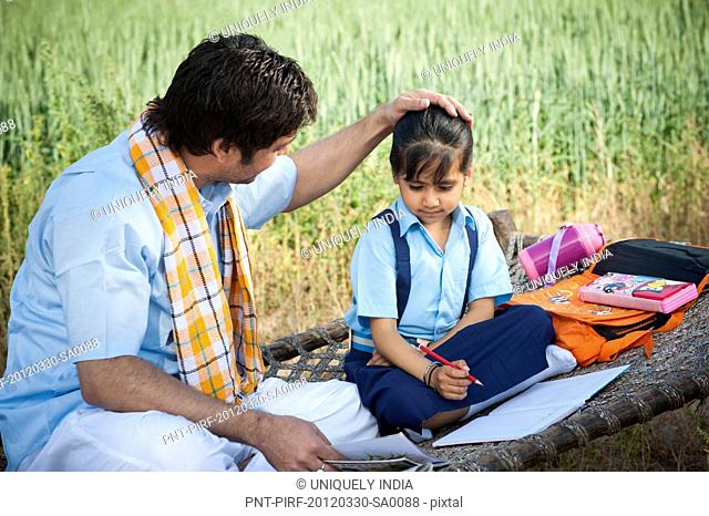 Farmer teaching his daughter in the field, Sohna, Haryana, India