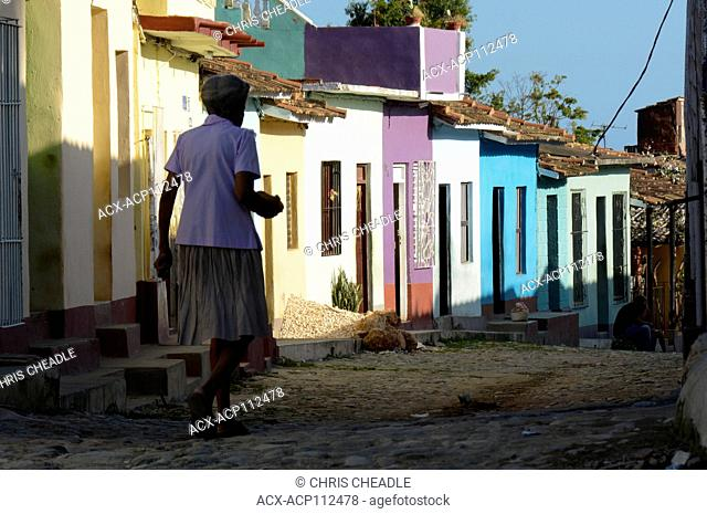 Older woman walks by colorful house fronts, Trinidad, Cuba