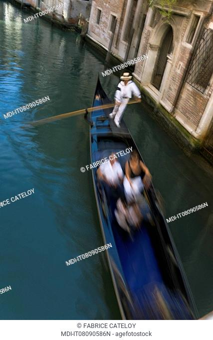 Gondolier with tourists in a canal of the town