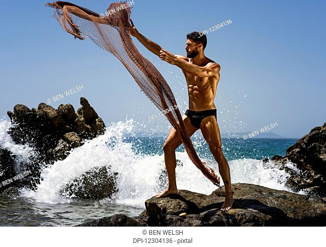 A muscular man in a bathing suit throwing a net into the water while standing on a rock at the coast; Tarifa, Cadiz, Andalusia, Spain