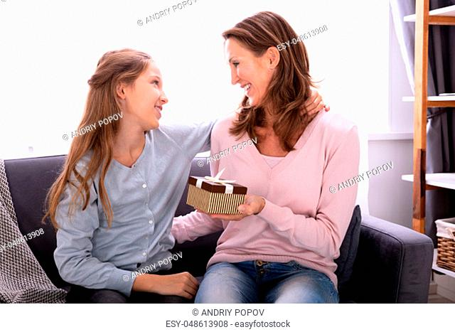 Portrait Of A Girl Giving Gift To Her Happy Mother