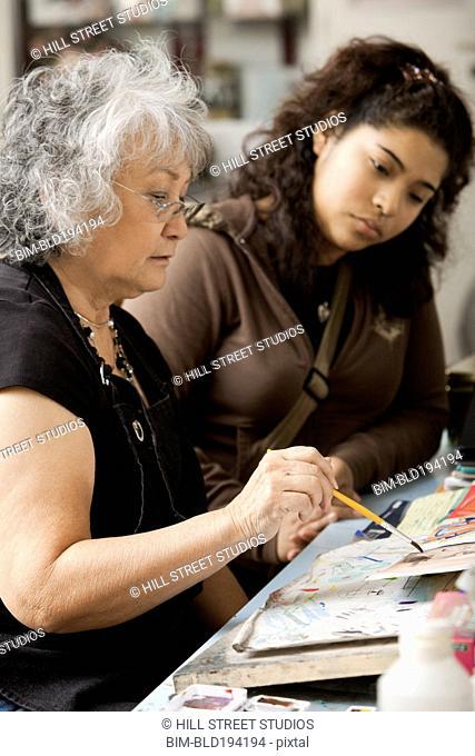 Student watching art teacher paint in classroom