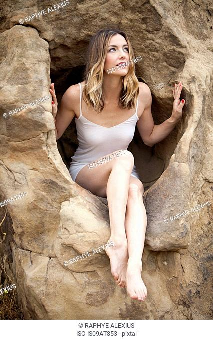 Woman sitting in rock formation, Stoney Point, Topanga Canyon, Chatsworth, Los Angeles, California, USA