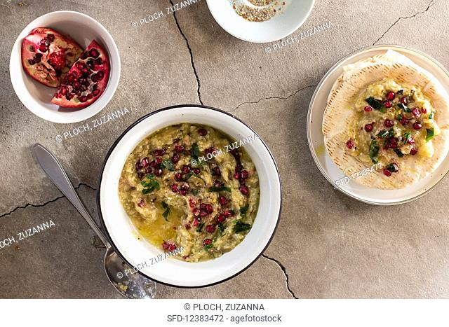 Baba ghanoush (aubergine dip) with pomegranate seeds, parsley, olive oil and pita bread