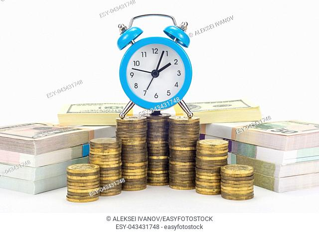 The clock is on a stack of coins, in the background are bundles of bills
