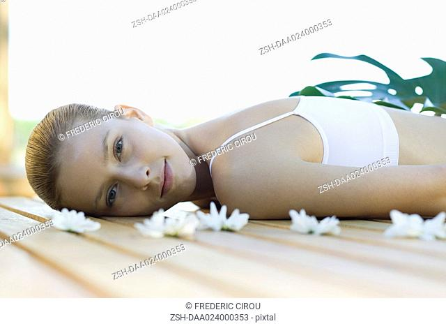 Woman lying on deck, surrounded by flowers