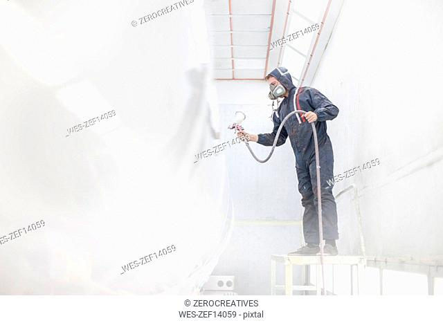 Industrial worker spray painting and wearing protective clothing