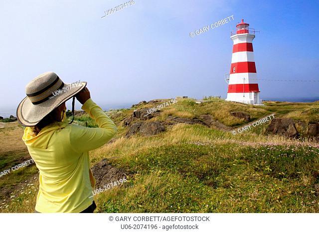 A woman looking through binoculars near the Brier Island Lighthouse at West Point, Brier Island, Nova Scotia, Canada