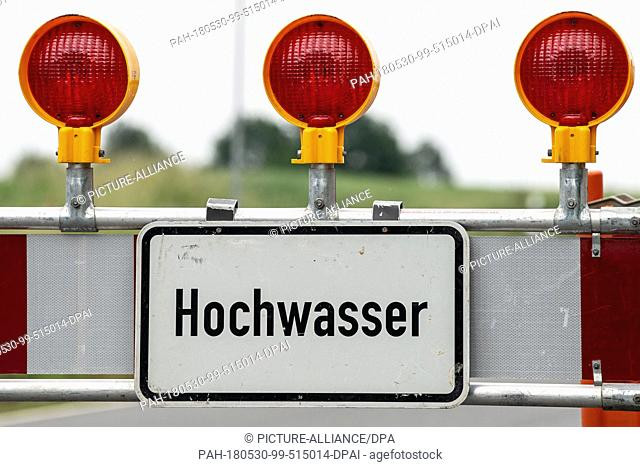 30 May 2018, Germany, Bad Gandersheim: A blockade with the sign 'hochwasser' (lit. high water) standing on the L635 road