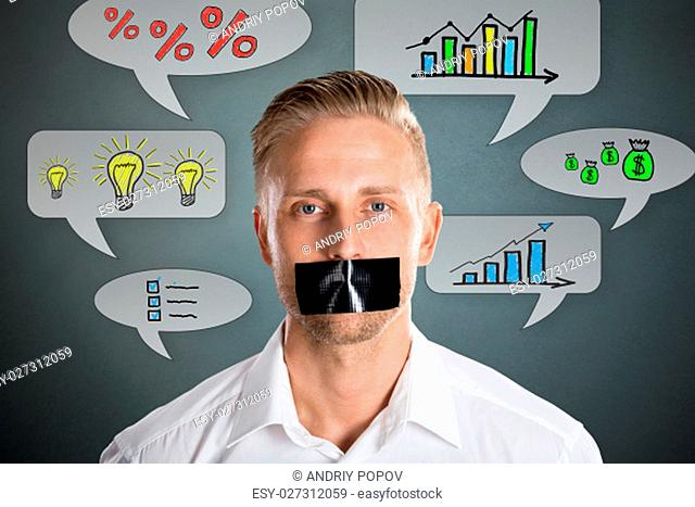 Businessman With Black Duct Tape Over His Mouth With Business Symbol At Background