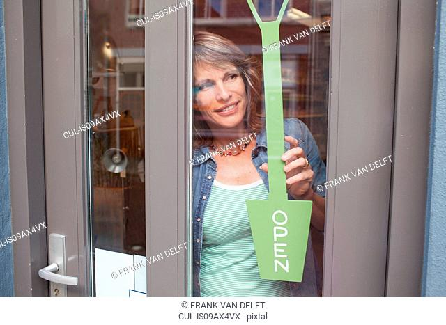 View through glass shop door of woman holding open sign