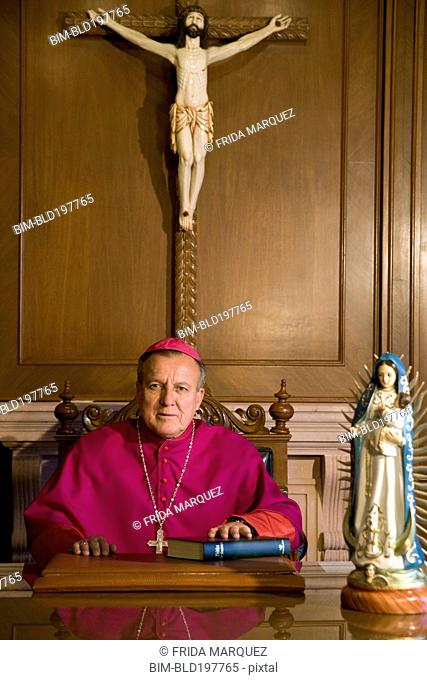 Hispanic bishop sitting with bible