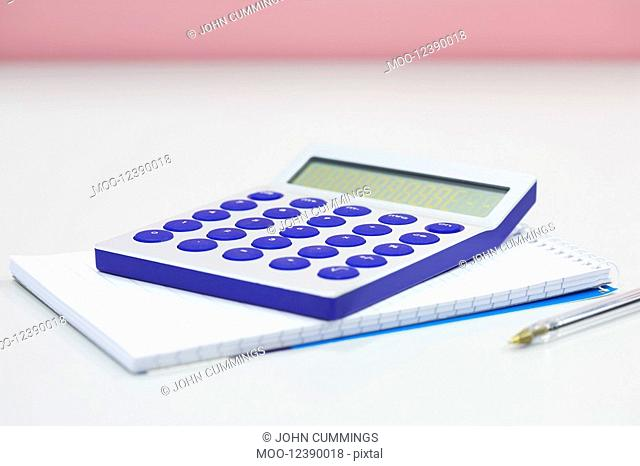 Calculator notebook and pen on table close up