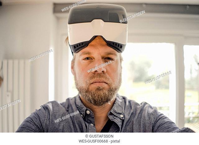 Mature man taking selfie of himself, wearing VR glasses, looking cool