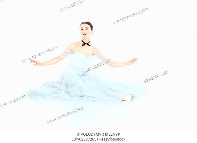 Ballerina in white dress sitting, studio white background