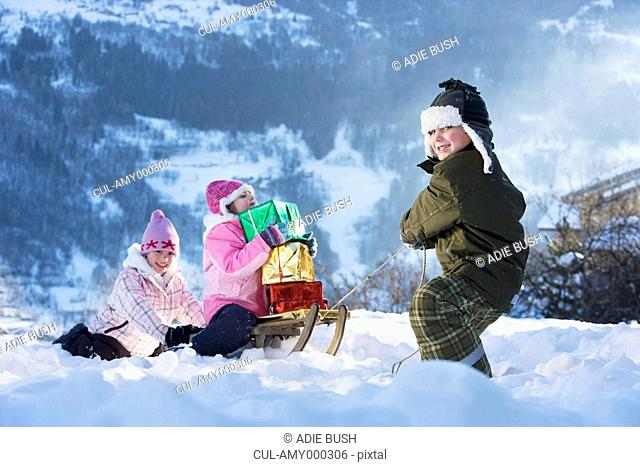 Children playing in snow with presents