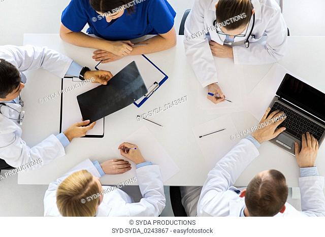 group of doctors with x-ray and laptop at clinic