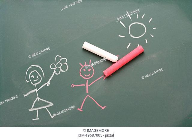Chalk drawing on blackboard of boy and girl