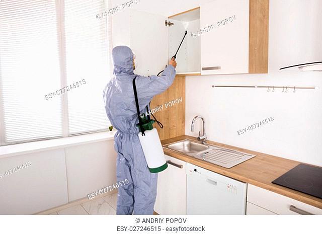Pest Control Worker In Workwear Spraying Pesticide On Shelf In Kitchen
