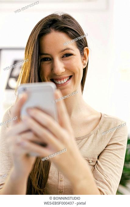 Portrait of young female entrepreneur with smartphone