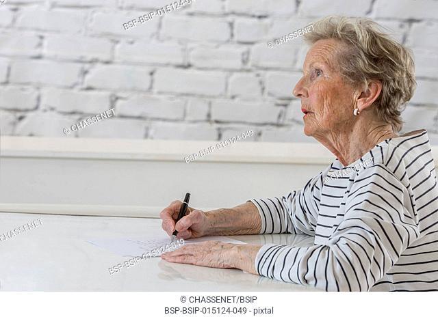Senior woman writing on a white sheet