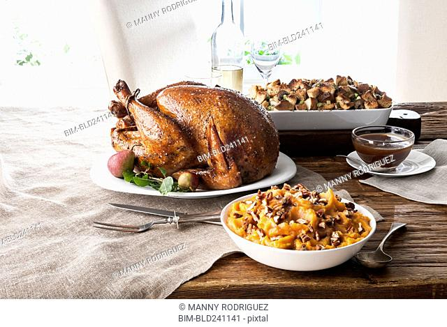 Stuffing, sweet potatoes and smoked turkey on wooden table