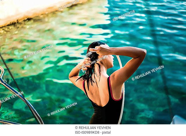 Young woman in bathing costume showering aboard yacht, Croatia