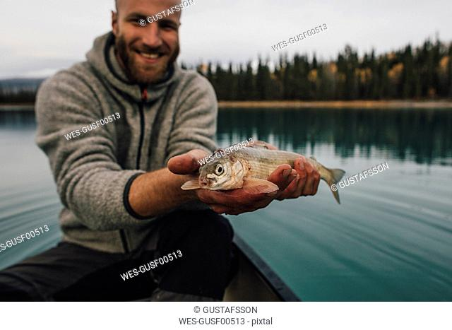 Canada, British Columbia, portrait of smiling man in canoe holding fish on Boya Lake