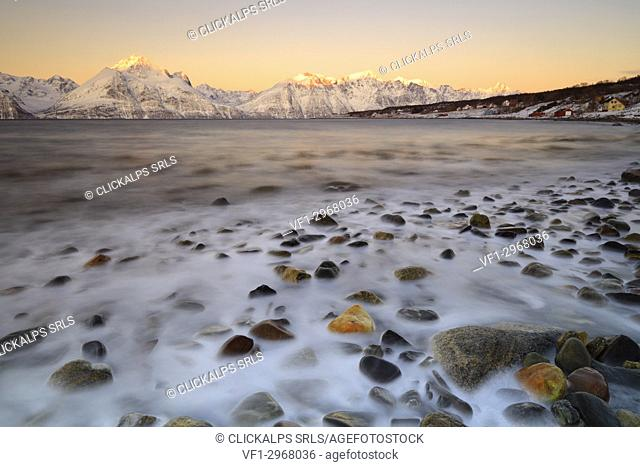 Cloudless sunrise with ice covering the stones on the shore of Balsfjorden. Markenes, Balsfjorden, Lyngen Alps, Troms, Norway, Lapland, Europe