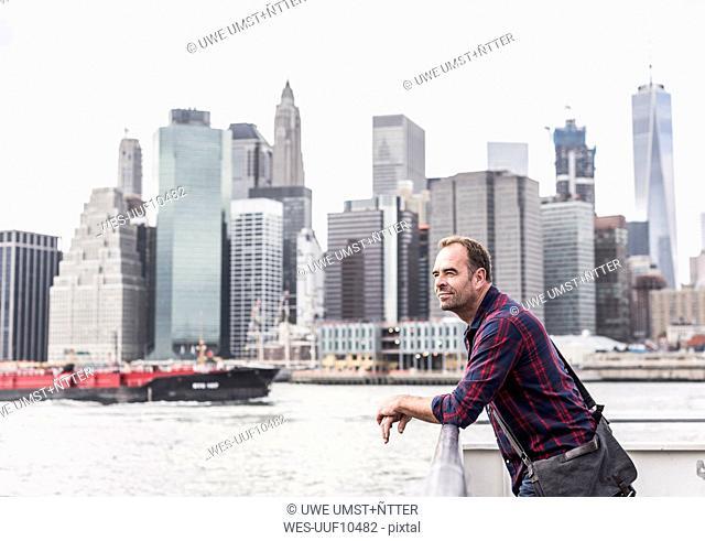 USA, New York City, man on ferry with Manhattan skyline in background