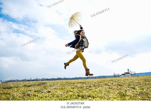 Teenage girl in field with umbrella