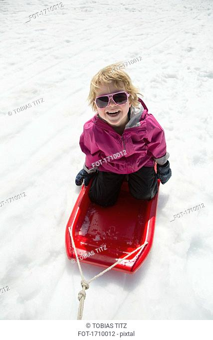 High angle view of cheerful boy tobogganing on snow covered field