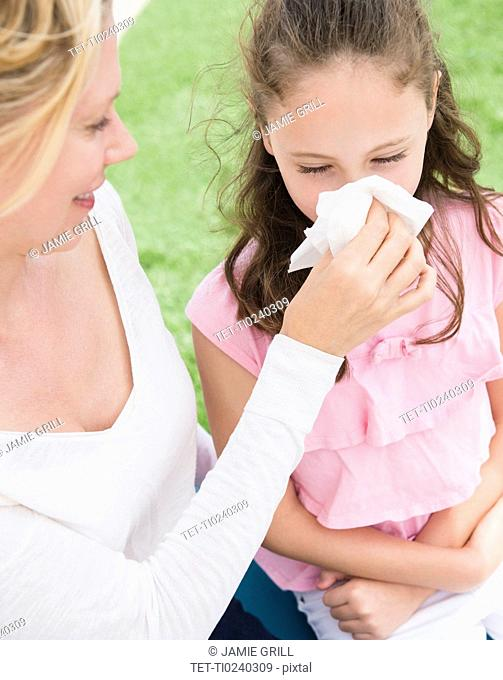Mother helping daughter 8-9 years to blow her nose