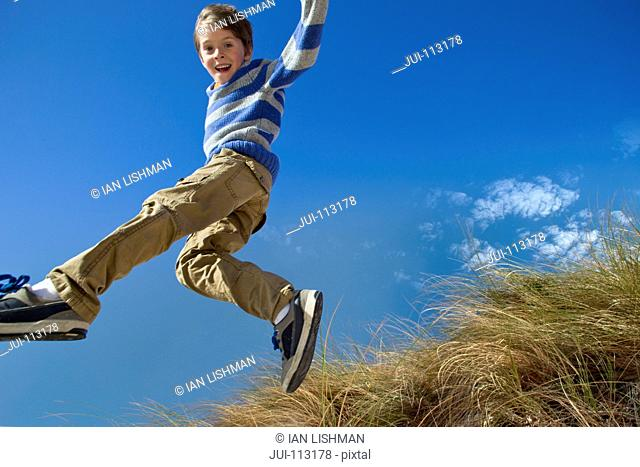 Exuberant boy jumping for joy over grass