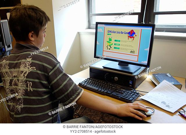 6th Grade Boy Working on Science Assignment at Computer, Wellsville, New York, USA