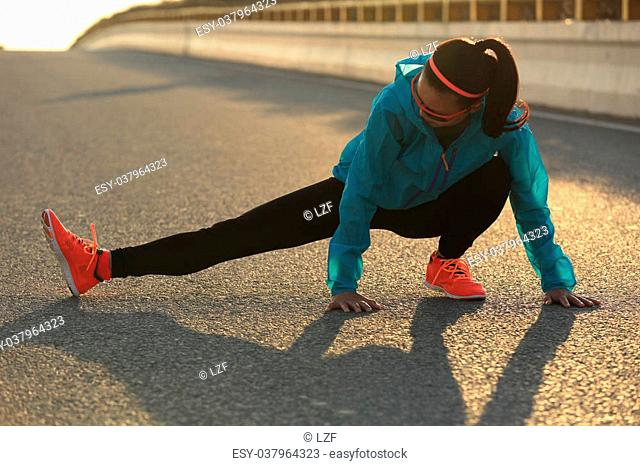 Young female runner stretching her legs on sunrise road