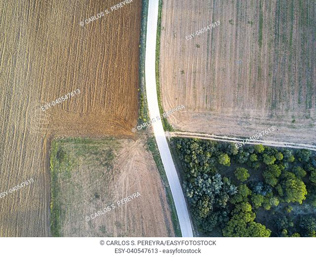 Abstract landscape made with an aerial shot with a drone of a rural road in the fields during the autumn in the province of Gerona in Catalonia Spain