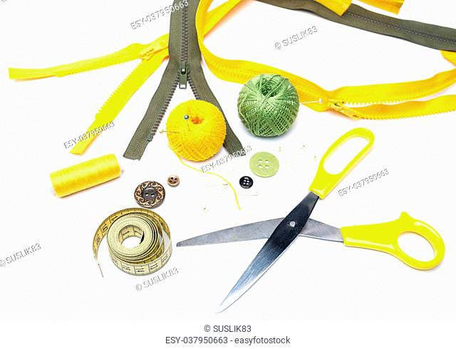 bunch of various sewing accessories - yellow measuring tape skeins yellow and green yarn, metal scissors, various buttons, and more - on a white background