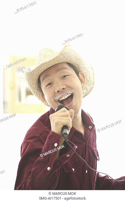 Man wearing hat, singing into microphone