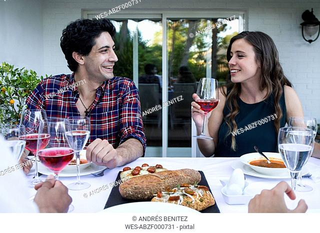 Man and woman having fun and drinking lambrusco wine during a summer dinner