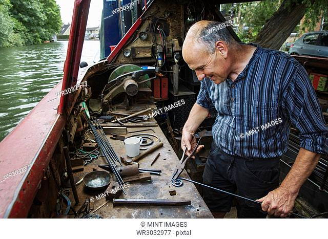Blacksmith in his floating workshop on a narrowboat, holding pliers and metal rod, working a metal object