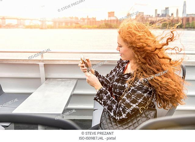 Young businesswoman on passenger ferry deck looking at smartphone