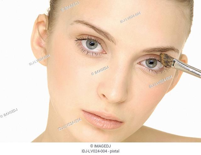 Portrait of a young woman applying eyeshadow