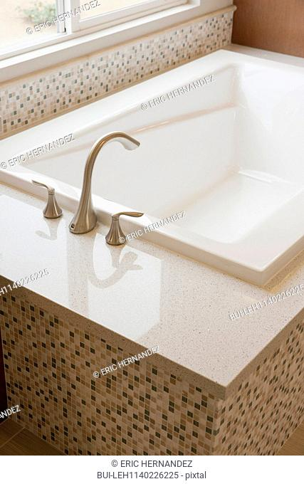 Close-up of a faucet and cropped bath in the bathroom