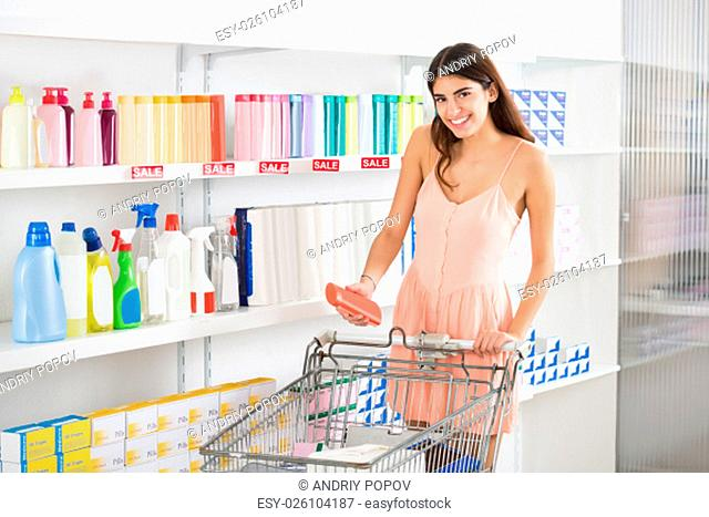 Smiling young woman with shopping cart buying beauty product in supermarket