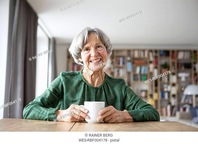 Portrait of smiling senior woman sitting at table with cup of coffee