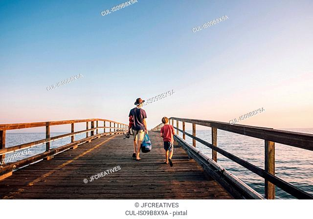 Rear view of father and son walking on pier, Goleta, California, United States, North America