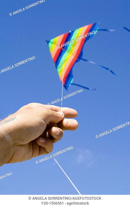 Man's hand holding a kite againste the blue sky, focoused on the hand