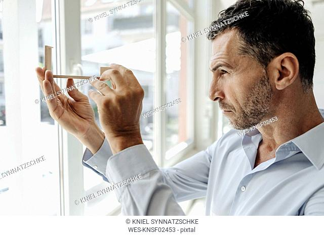 Businessman at the window looking at architectural model