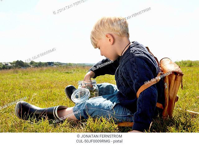 Boy filling jar in grassy field